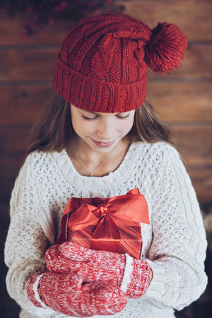 holiday house: Child giving a Christmas present on rustic wooden background, farmhouse interior.