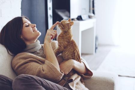 Người phụ nữ trẻ mặc áo len ấm áp được nghỉ ngơi với một con mèo trên chiếc ghế bành ở nhà một ngày mùa thu