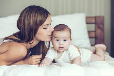 肖像漂亮媽媽的吻她5個月大的嬰兒在床上