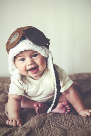 Portrait of a lovable 5 months baby in funny pilot hat, toned image