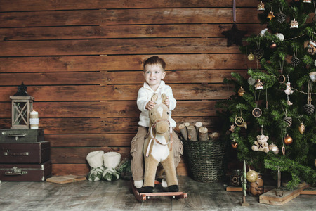 wooden toy: 3 years old child celebrating holidays near Christmas tree, farm house design