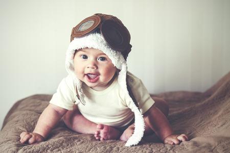 ojos marrones: Imagen del retrato de un adorable bebé de 5 meses en el sombrero divertido piloto, tonificado