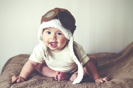 beautiful eyes: Portrait of a lovable 5 months baby in funny pilot hat, toned image