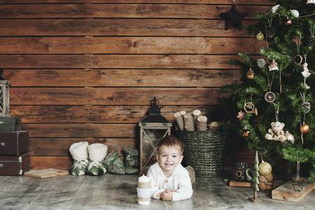 room decoration: 3 years old child celebrating holidays near Christmas tree, farm house design