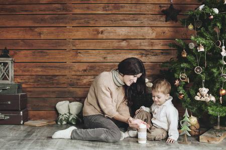 mama e hijo: Madre firh sus 3 años de edad hijo la celebración de fiestas cerca de árbol de Navidad, diseño de casa de la granja Foto de archivo