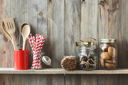 Kitchen cooking utensils in ceramic storage pot and cookies on a shelf on a rustic wooden wall Banco de Imagens