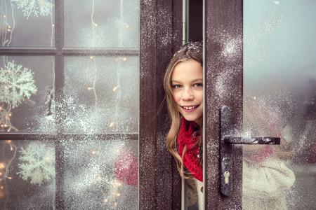 Kind meisje opent dor en welkome gasten, sneeuw weer wordt het huis ingericht voor Kerstmis Stockfoto