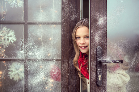 Child girl opens dor and welcome guests, snow weather, house is decorated for Christmas Archivio Fotografico