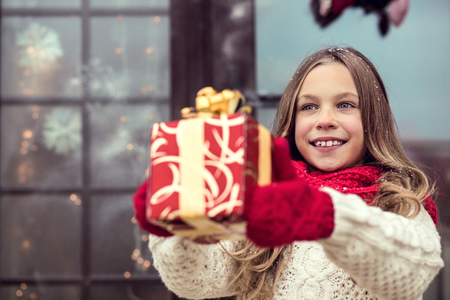christmas scene: Child giving a Christmas present near her house windows, snowy outside Stock Photo