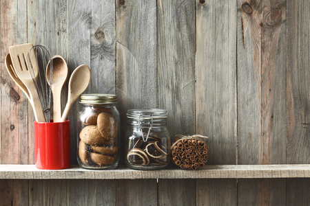 Utensilios de cocina de cocina en una olla de cerámica de almacenamiento y galletas en un estante en una pared de madera rústica