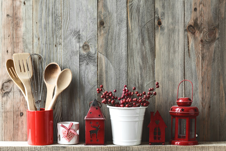 vintage timber: Kitchen cooking utensils in ceramic storage pot and Christmas decor on a shelf on a rustic wooden wall