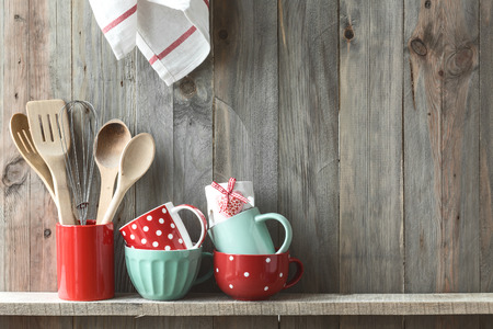 red kitchen: Kitchen cooking utensils in ceramic storage pot on a shelf on a rustic wooden wall, space for text