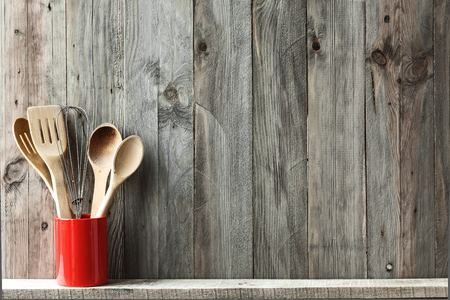 Kitchen cooking utensils in ceramic storage pot on a shelf on a rustic wooden wall, space for text