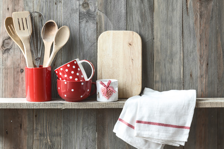 utensils: Kitchen cooking utensils in ceramic storage pot on a shelf on a rustic wooden wall Stock Photo