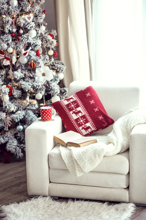 Opened book and a cup of tee on the cozy chair with warm blanket and cushion on it near Christmas tree Stock Photo