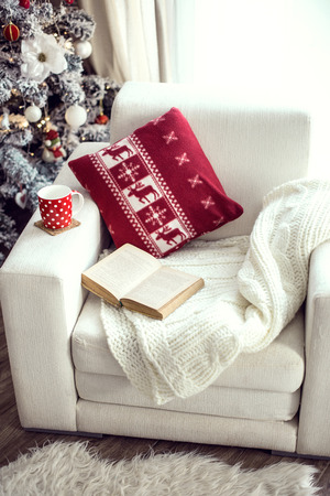 scandinavian christmas: Opened book and a cup of tee on the cozy chair with warm blanket and cushion on it near Christmas tree Stock Photo