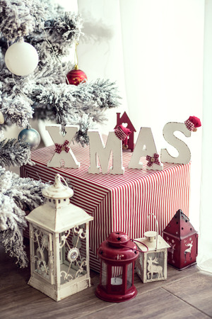 details: Wrapped gift with wooden letters XMAS and holiday lanterns under Christmas tree Stock Photo