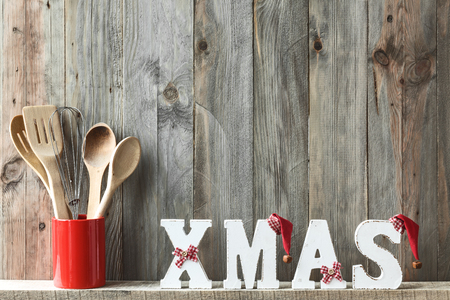 christmas decor: Kitchen cooking utensils in ceramic storage pot and Christmas decor on a shelf on a rustic wooden wall