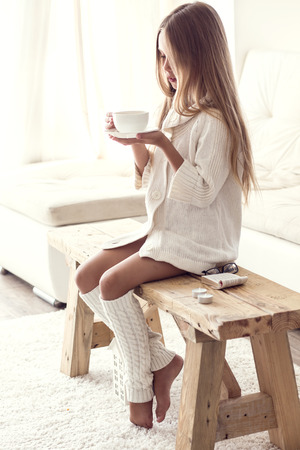 Pretten girl wearing warm knitted clothing is sitting on rustic chair on a carpet and relaxing in white living room. Winter weekend.