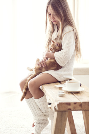 Pretten girl wearing warm knitted clothing is sitting on rustic bench with her cat in white living room. Winter weekend.