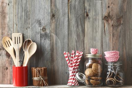 especias: Utensilios de cocina de cocina en una olla de cerámica de almacenamiento y galletas en un estante en una pared de madera rústica