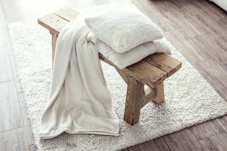 Detalles Naturaleza muerta, pila de cojines blancos y una manta en el banco rústico en la alfombra blanca Foto de archivo