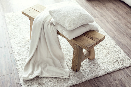 bedding: Still life details, stack of white cushions and blanket on rustic bench on white carpet