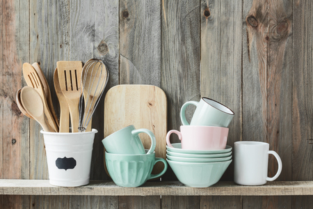 Kitchen cooking utensils in ceramic storage pot on a shelf on a rustic wooden wall Standard-Bild
