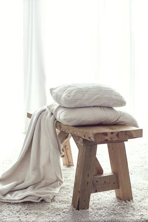 muebles de madera: Detalles Naturaleza muerta, pila de cojines blancos y una manta en el banco rústico en la alfombra blanca