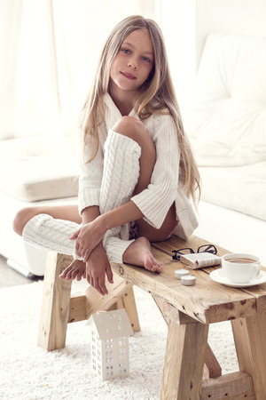 clothing model: Preteen girl wearing warm knitted clothing is sitting on rustic chair on a carpet and relaxing in white living room. Winter weekend.
