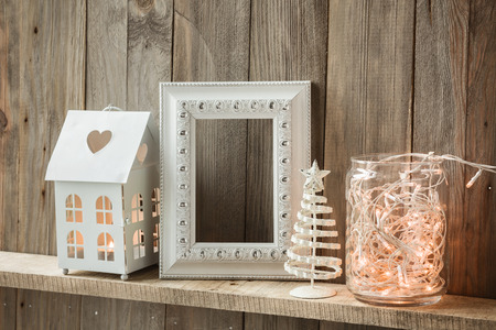 Sweet home. White Christmas decor on vintage natural wooden background. Empty photo frame. Stock Photo