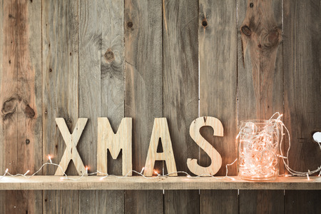 wall decoration: Sweet home. White Christmas decor and fairy lights on vintage natural wooden background. Stock Photo