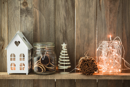 jars: Sweet home. White Christmas decor on vintage natural wooden background. Cinnamon sticks and dried citrus. Cafe shelf. Stock Photo