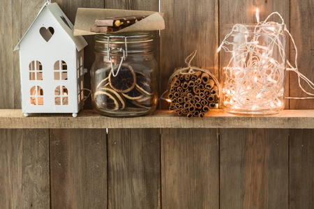 Sweet home. White Christmas decor on vintage natural wooden background. Cinnamon sticks and dried citrus. Cafe shelf. Space for custom text. 版權商用圖片