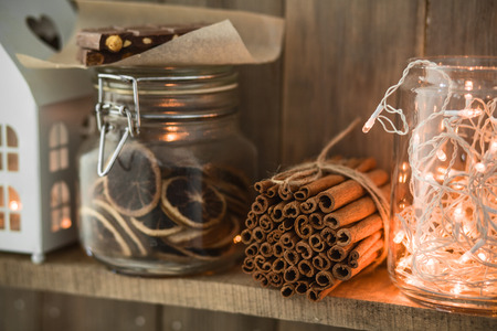 lights on: Sweet home. White Christmas decor on vintage natural wooden background. Cinnamon sticks and dried citrus. Cafe shelf. Selective focus. Stock Photo