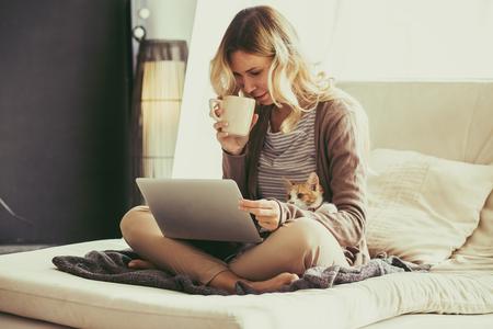 trabajando en casa: Mujer joven feliz que se relaja en el sof� c�modo y usando la computadora port�til en casa. Foto entonada. Foto de archivo