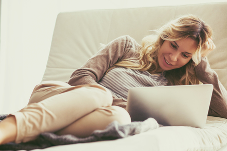 livingroom: Happy young woman is relaxing on comfortable couch and using laptop at home. Photo toned.