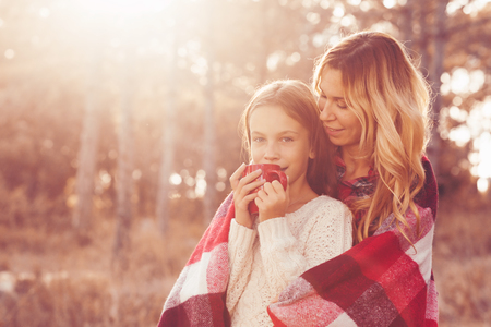 Mom and her 9 years old daughter spending weekend in the autumn forest together. Mother and child relations.