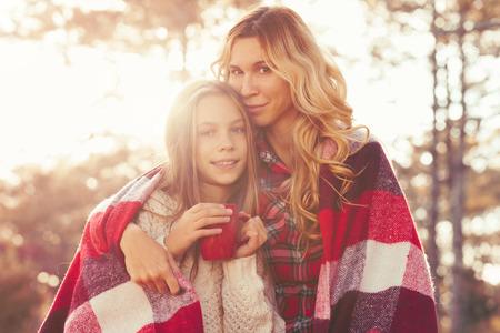 媽媽和她9歲的女兒週末支出在秋季森林在一起。母親和孩子的關係。