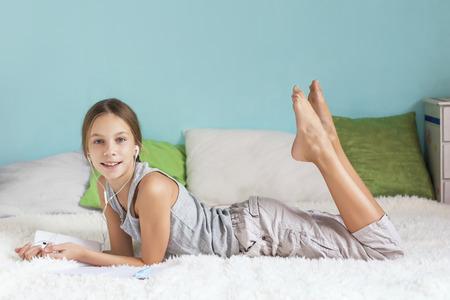 niños malos: Muchacha pre adolescente es relajante en la cama y escuchar música con auriculares en la tablilla en el país