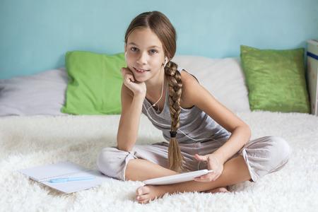 前の十代の少女は、ベッドでくつろぎ、タブレットを自宅でイヤホンで音楽を聴く