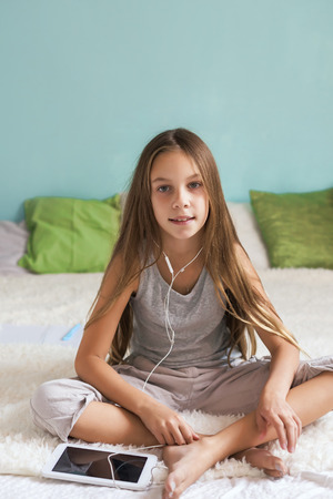pre teen girls: Pre teen girl is relaxing in the bed and listening to music with earphones on the tablet at home
