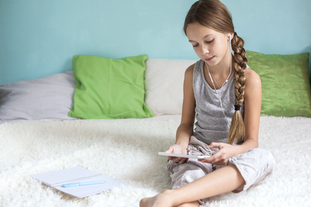 pre school: Pre teen girl is relaxing in the bed and listening to music with earphones on the tablet at home