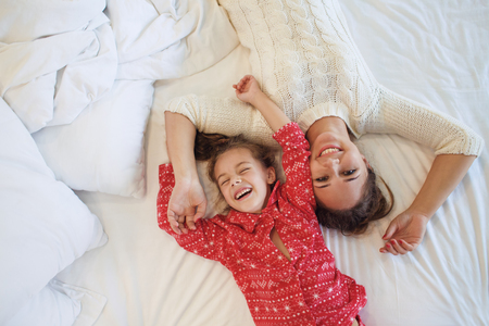 6 year old children: Mom with her 6 years old little daughter dressed in winter pajamas are relaxing and playing in the bed at the weekend together, lazy morning, warm and cozy scene. Top view point.