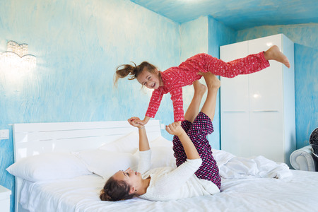 perezoso: Mam� con su peque�a hija de 6 a�os de edad vestido con pijama de invierno son relajantes y jugando en la cama en el fin de semana juntos, ma�ana tranquila, c�lida y acogedora escena. Foto de archivo