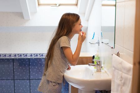 dientes sanos: Muchacha pre adolescente lava los dientes en el ba�o del hotel Foto de archivo