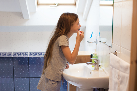 teeth cleaning: Pre teen girl brushes her teeth in the hotel bathroom Stock Photo