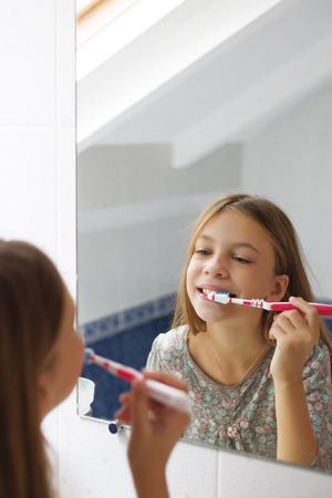 pre teen: Pre teen girl brushes her teeth in the hotel bathroom Stock Photo