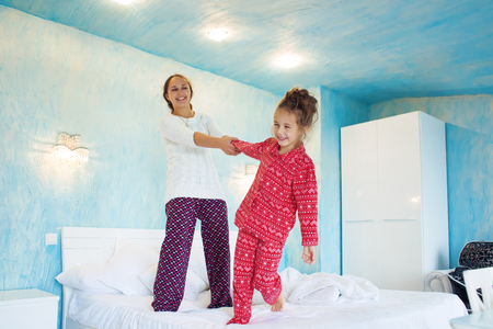 6 years: Mom with her 6 years old little daughter dressed in winter pajamas are relaxing and playing in the bed at the weekend together, lazy morning, warm and cozy scene.