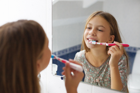 mouths: Pre teen girl brushes her teeth in the hotel bathroom Stock Photo